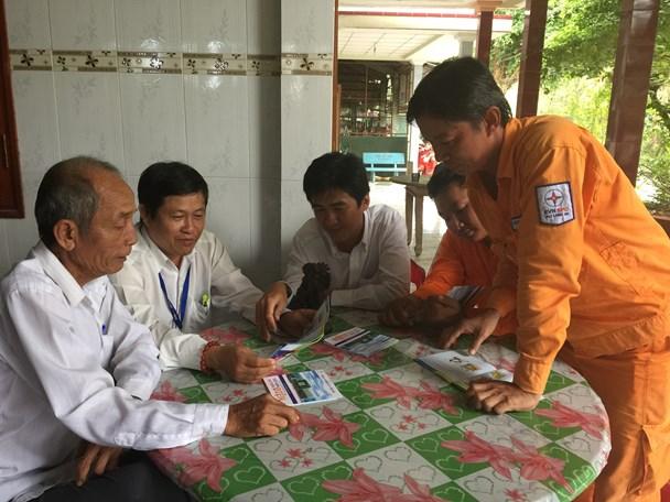 Nhân viên Điện lực Tân An giới thiệu các tờ rơi về sử dụng điện tiết kiệm cho ông Hai Nên. Ảnh: AN NHIÊN