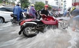 Mưa lớn, nước chảy xiết cuốn trôi xe máy ở Sài Gòn