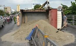 TPHCM: Xe tải chở cát lật ngược trên cầu vượt