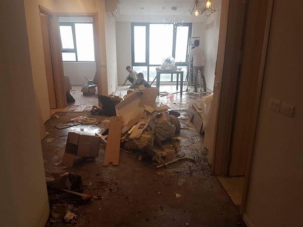 Những hình ảnh ngổn ngang do nước ngấm vào sàn gỗ của căn hộ gây hỏng hóc đang được chủ đầu tư sửa chữa lại. (Ảnh cư dân cung cấp). Cho đến thời điểm 18h30 cùng ngày, tình trạng cư dân tụ tập phản đối chủ đầu tư vẫn tiếp tục diễn ra.